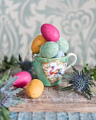 Colourful speckled eggs in gold-rimmed teacup and Eryngium flower on rustic wooden surface