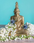 Buddha figurine arranged with white flowers and Eryngium flowers against turquoise background