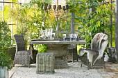 Wintergarten mit Kiesfläche und Rattanstühlen um massiven Steintisch