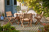 Sunny seating area on terrace outside traditional country house
