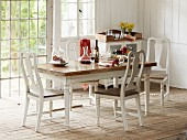 Set dining table in country house with rustic wooden floor and white wood-clad walls