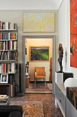 Bookcase and terrazzo floor in elegant living area with view of armchair through open door