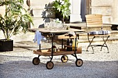 Serving trolley on castors in gravel courtyard