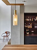 Drinks cabinet in open-plan kitchen, pendant lamp above dining table and designer chair in background