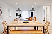 Dining table with metal frame and wooden top, wooden bench and wooden chairs in open-plan interior