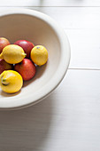 Lemons and apples in white fruit bowl on white table