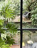 Blick durchs Fenster auf Hinterhofgarten mit zwei Ebenen