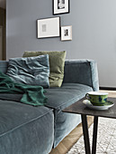 Cushions on velvet sofa in front of pictures on grey wall