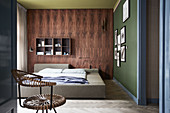 Wood-panelled wall and green wall with pictures in bedroom