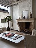 Couchtisch vor Kamin in Loft-Wohnzimmer mit weiss gestrichener Ziegelwand