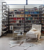 Custom bookshelves, classic recliner and side table on cowhide rug in loft apartment
