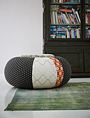 Pouffe with different patterns on green rug in front of cabinet