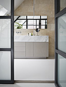 View through open glass door into modern bath with simple, clean lines