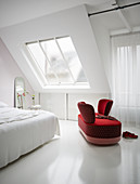 Red loveseat in white bedroom
