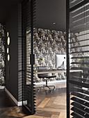 Blick ins Büro mit gemusterter Tapete und Glaswänden mit Jalousien