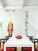 White dining table, chairs, tailors' dummy and pattern of stickers on glass partition