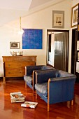 Two blue leather armchairs in front of old chest of drawers and blue picture