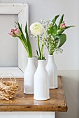 Ranunculus, tulips and gypsophila in three white bottles