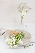 White ranunculus and gypsophila in stone bowl