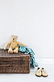 Teddy bear and checked shirt on wicker trunk next to white shoes