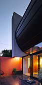 Architect-designed house with glass wall at dusk