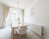 Shell chairs around dining table in front of classic arched window