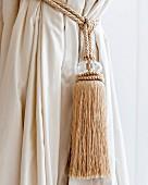 Cremefarbene Quaste mit Kordel am Vorhang