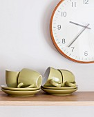 Green espresso cups and saucers below wall clock