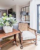 Alter Holzsessel neben einem Holztisch mit grünem Strauß