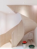 Designer chair and roses under modern curved staircase