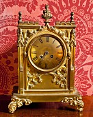 Ornate gilt table clock with Roman numerals against red brocade wallpaper