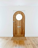 Front door with round window in empty room with oak parquet floor
