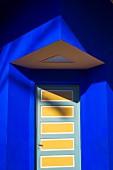 Front door below porch on corner of house painted ultramarine