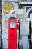 Red, English, vintage petrol pump in front of yellow enamel sign on façade