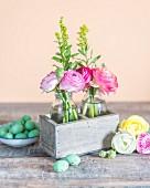 Österliche Tischdekoration mit rustikalem Flair und zarten Ranunkelblüten