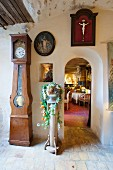 Antique long-case clock in foyer with view into cafe