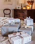 Verpackte Geschenke in Grau, Silber und Weiß im Schlafzimmer