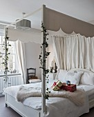 Wrapped presents on white four-poster bed with canopy decorated with ivy tendrils