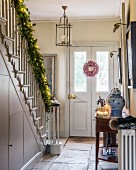 Festively decorated hall with garland along staircase handrail