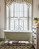 Free-standing bathtub in front of French window with shutters