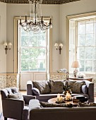Cosy lounge with bay window, sofas, armchairs and lit candles on coffee table