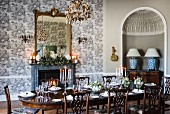 Set table in elegant dining room with toile de jouy wallpaper