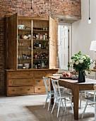 Rustikaler Holzschrank mit geöffneter Tür und Esstisch in geräumiger Küche mit Ziegelwand