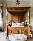 Ornate four-poster bed with cushions in bedroom with bay window and buttoned-tufted stool