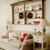 Plate rack on wood-clad wall above sofa with scatter cushions in shades of red