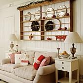 Tellerregal an Bretterwand über dem Sofa mit roten Kissen