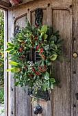 Festive wreath on rustic wooden front door