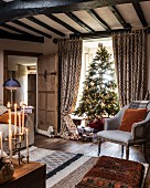 Christmas tree in living room with wood-beamed ceiling