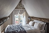 Fur blanket on bed below chandelier in attic bedroom