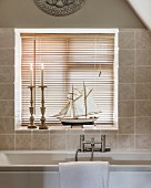 Candlesticks and model boat in front of louvre blinds on windowsill of bathroom window